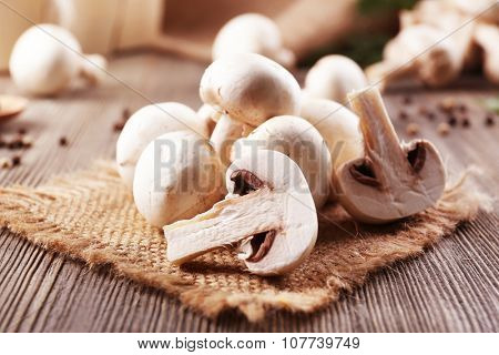Champignon mushrooms, sacking mat and spices on wooden background