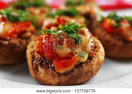 A plate with stuffed mushrooms on wooden background, close-up