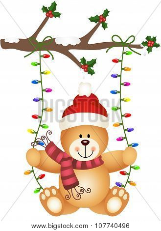 Teddy bear swinging on Christmas lights