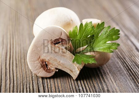Champignon mushrooms and parsley on grey wooden background
