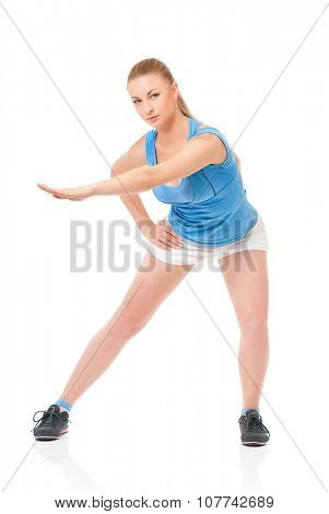 Smiley young sportswoman doing stretching exorcises, isolated on white background