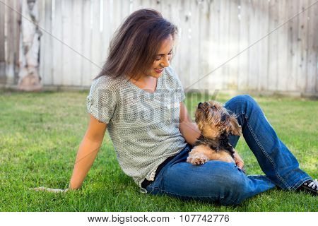 Young girl and her dog sitting in the grass