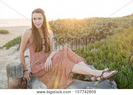 Girl sitting by the beach at sunset