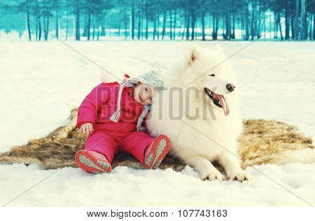 Child With White Samoyed Dog Having Fun On Snow In Winter Day