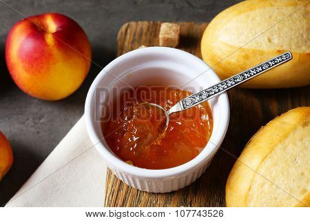 Tasty jam in the bowl, ripe peach, crackers and fresh buns close-up