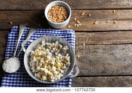 Salted popcorn in a metal bowl with cup of corns on checked cotton napkin on wooden table