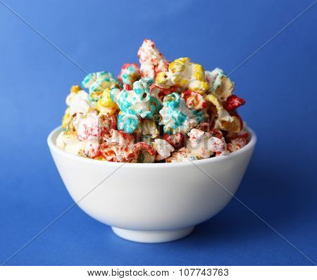 Sweet colourful popcorn on blue background