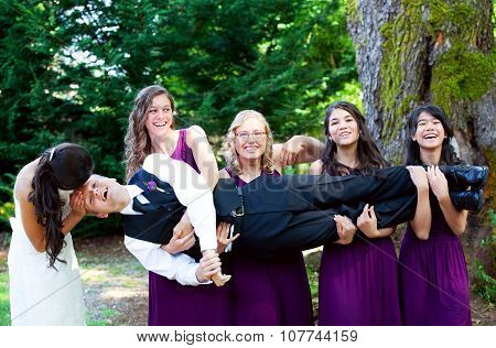 Four Bridesmaids Carrying Groom In Their Arms