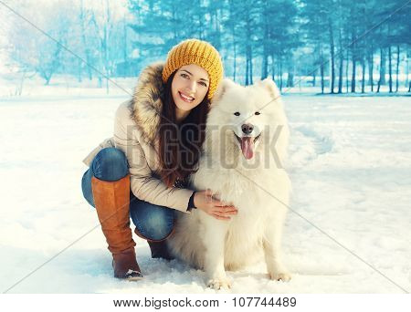 Happy Smiling Woman Owner Embracing White Samoyed Dog In Winter Day
