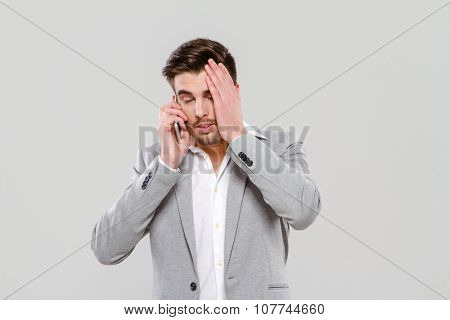 Exhausted handsome young businessman in gray jacket and white shirt talking on mobile phone