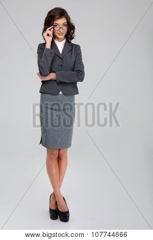 Full length portrait of young pretty curly smiling business woman touching her glasses