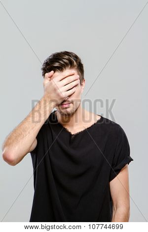 Young handsome man doing facepalm covering his eyes and face with palm