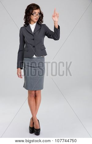 Confident curly pretty business woman in glasses and gray suit touching copyspace by finger and standing with crossed legs