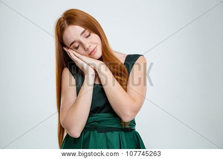 Portrait of a young redhair woman standing and sleeping isolated on a white background