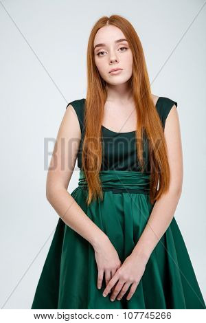 Portrait of a sad redhair woman in dress looking at camera isolated on a white background