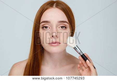 Portrait of a young redhair woman using makeup brush isolated on a white background