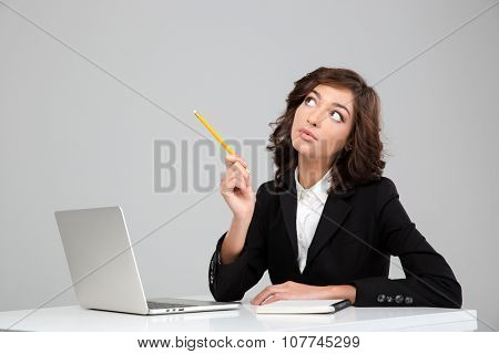Thoughtful concentrated curly pretty young woman in black jacket planning using laptop and notebook