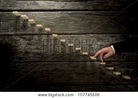 Businessman Walking His Fingers Up Wooden Steps Towards Light