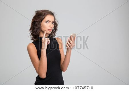 Annoyed young curly woman in black top using cellphone