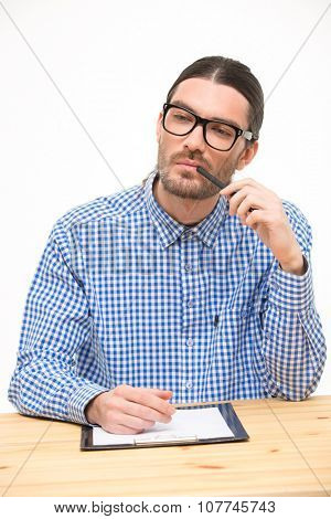 Thinking handsome young man in glasses and checked shirt sitting at the desk