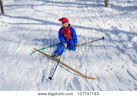 Girl sitting down on the snow learning skiing