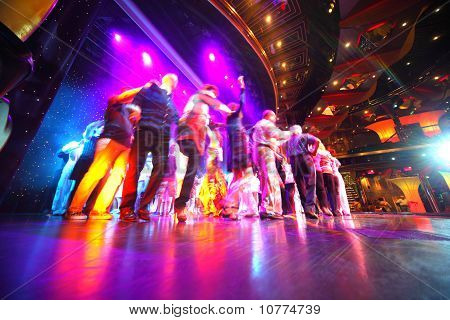 People Crowd Dance At An Illuminated Stage Of Restaurant On Cruise Ship