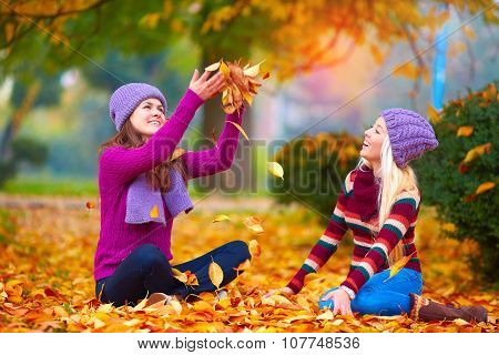 Pretty Girls, Friends Having Fun In Colorful Autumn Park, Tossing The Leaves Up