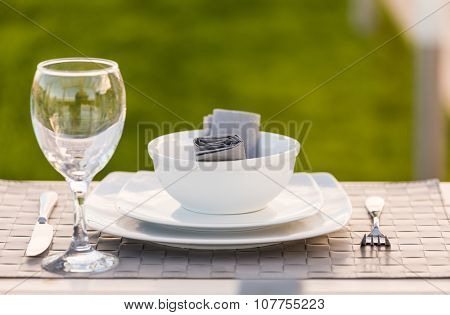 Elegant white tableware bowl, plates and wine glass set on table