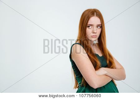 Offended woman redhair standing with arms folded isolated on a white background