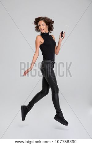 Happy beautiful smiling curly carefree girl in black clothes in jump listening music