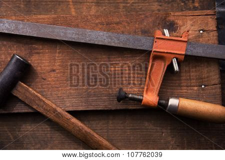 Woodworking or carpentry. Bar clamp and Hammer on rustic piece of wood. Shot in low key and shallow depth of field.