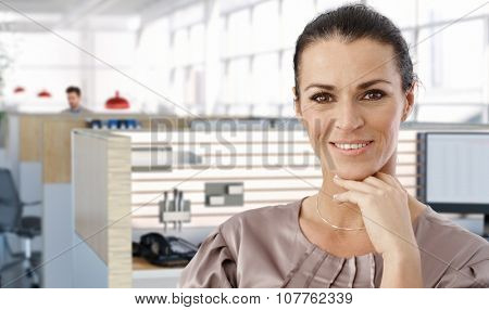 Portrait of middle aged female office worker in office cubicle, smiling.