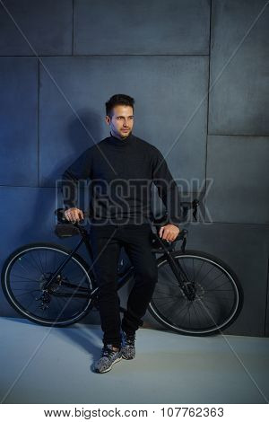 Young man waiting by wall, leaning against bicycle, looking away.
