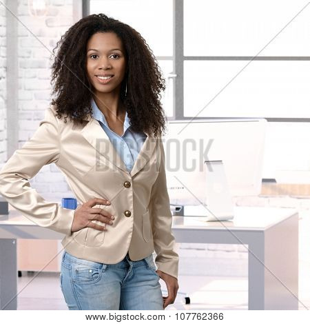 Female afro office worker posing for portrait at office desk, smiling.