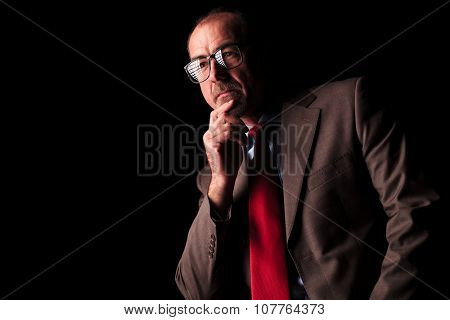 side view of a thoughtful senior business man looking away from the camera on black studio background