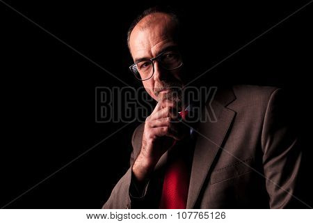 serious old business man thinking, against black studio background
