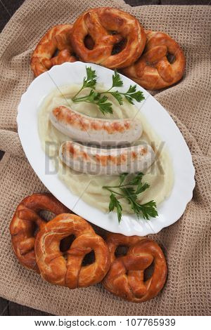 White german sausage with mashed potato and pretzel