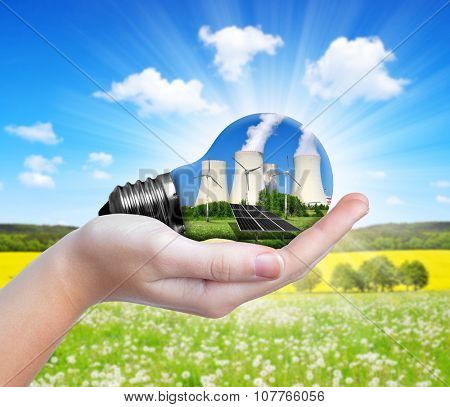 Hand holding lightbulb. Energy resources concept.