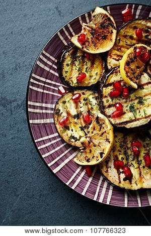 Grilled aubergine marinated in olive oil with ramsons and pomegranate seeds
