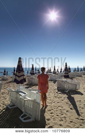 Woman stands on sunny beach with sun loungers and umbrellas