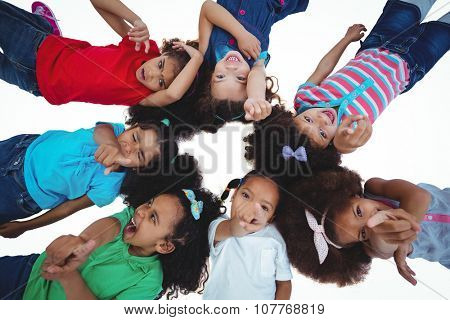 Small group of girls lying down looking upwards against a white background