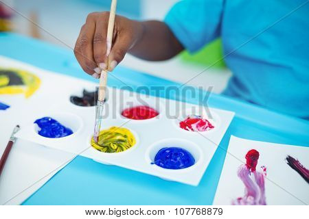 Happy kid enjoying arts and crafts painting at their desk