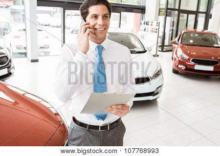 Smiling businessman on the phone holding clipboard at new car showroom