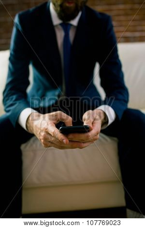 Businessman texting on the couch at home in the living room
