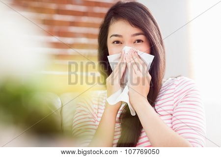 Asian woman blowing her nose on couch at home in the living room