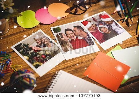 Snow falling against high angle view of office supplies with blank instant photos