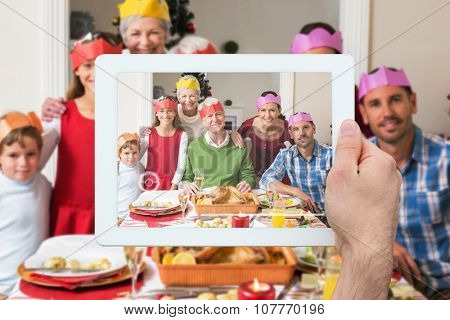 Hand holding tablet pc against happy extended family in party hat at dinner table