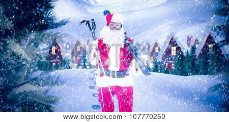 Santa claus holding ski and ski poles against cute village in the snow