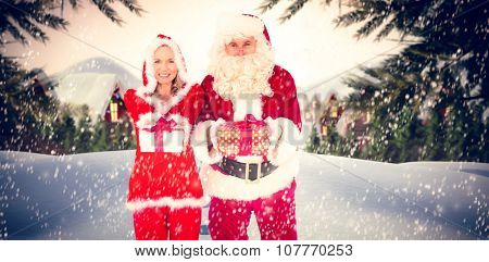 Santa and Mrs Claus smiling at camera offering gift against cute village in the snow