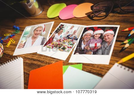 High angle view of office supplies and blank instant photos against smiling mature woman in santa hat toasting with white wine